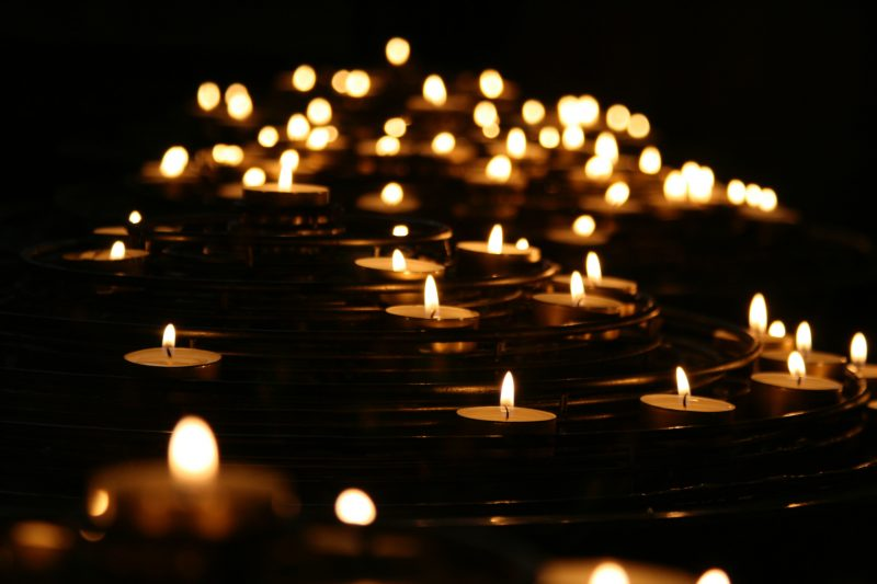 dozens of lit tea lights illuminate an otherwise dark background